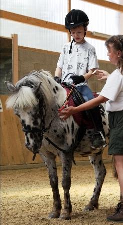 Lehrkraft und Reitkind beim HIPPOLINI®-Kurs - Feinfühliges Reiten am Pony erklärt